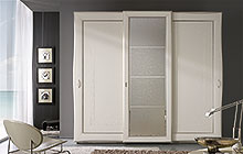 Wardrobe with 3 sliding doors, antique white finish with silver frame edging with decorative band of stucco reliefs and central panel.