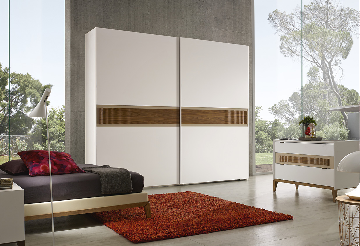DESIGNER WALTER TURINI <br> Wardrobe with 2 sliding doors, white matt lacquered finish (L01), section with dove grey lacquered finish (L80) and handle in waved Canaletto walnut. Wardrobe with 2 sliding doors, white matt lacquered finish (L01), section with dove grey lacquered finish (L80) and handle in waved Canaletto walnut.