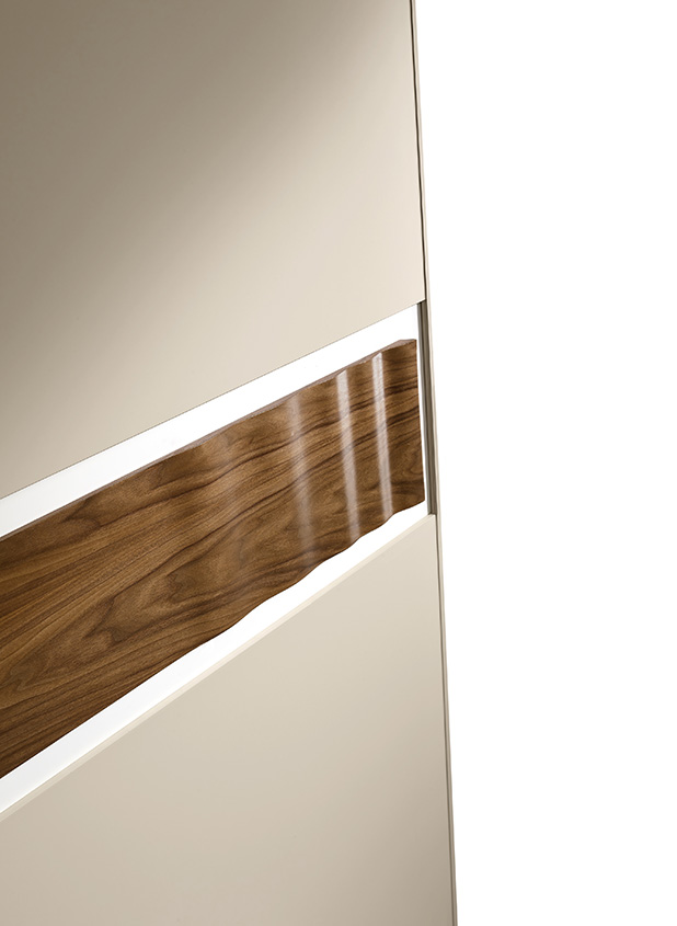 Details of wardrobe door, handle and section in waved Canaletto walnut.