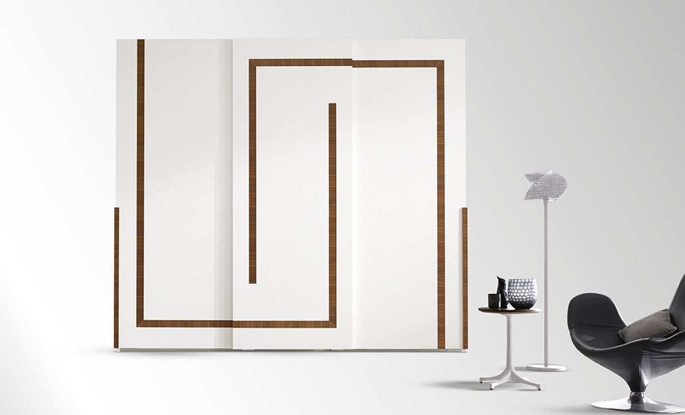 DESIGNER LEONARDO CIAMPI <br> Wardrobe with 3 sliding doors, geometric sections in Canaletto walnut. Available with or without central mirror.
