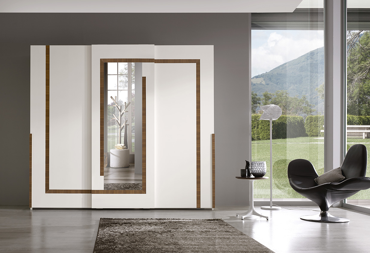 DESIGNER LEONARDO CIAMPI <br> Wardrobe with 3 sliding doors, white matt lacquered finish (L01) and central mirror. Side door handles in solid Canaletto walnut.