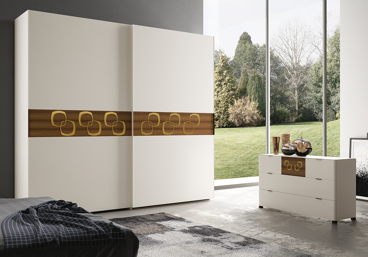 DESIGNER WALTER TURINI <br> Wardrobe with 2 sliding doors, white matt lacquered finish (L01), with central section in Canaletto walnut and metal inserts in gold leaf. <br> LEVANTE <br> Dresser with rounded-edge drawer fronts. PIXEL insert in Canaletto walnut applied to the top drawer. Top available in Canaletto walnut, in the various lacquered finishes and lacquered glass.