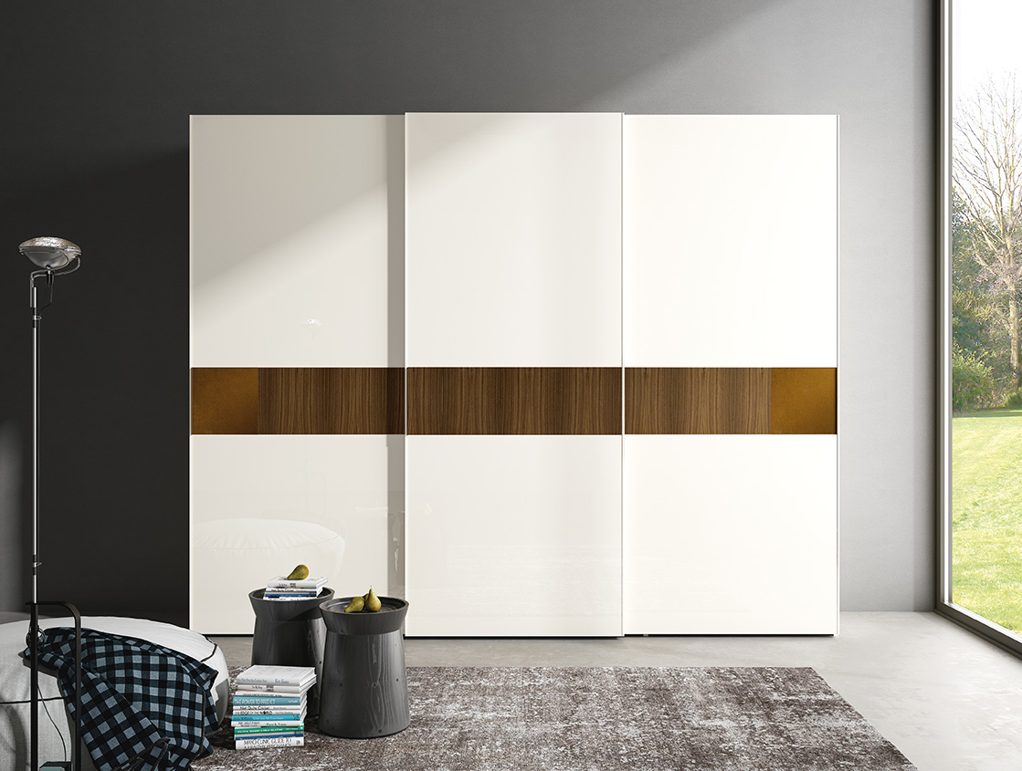 DESIGNER WALTER TURINI <br> Wardrobe with 3 sliding doors and central section in Canaletto walnut with vertical grain, matched with external tiles in bronze finish. Door with antique white lacquered glass (V062).
