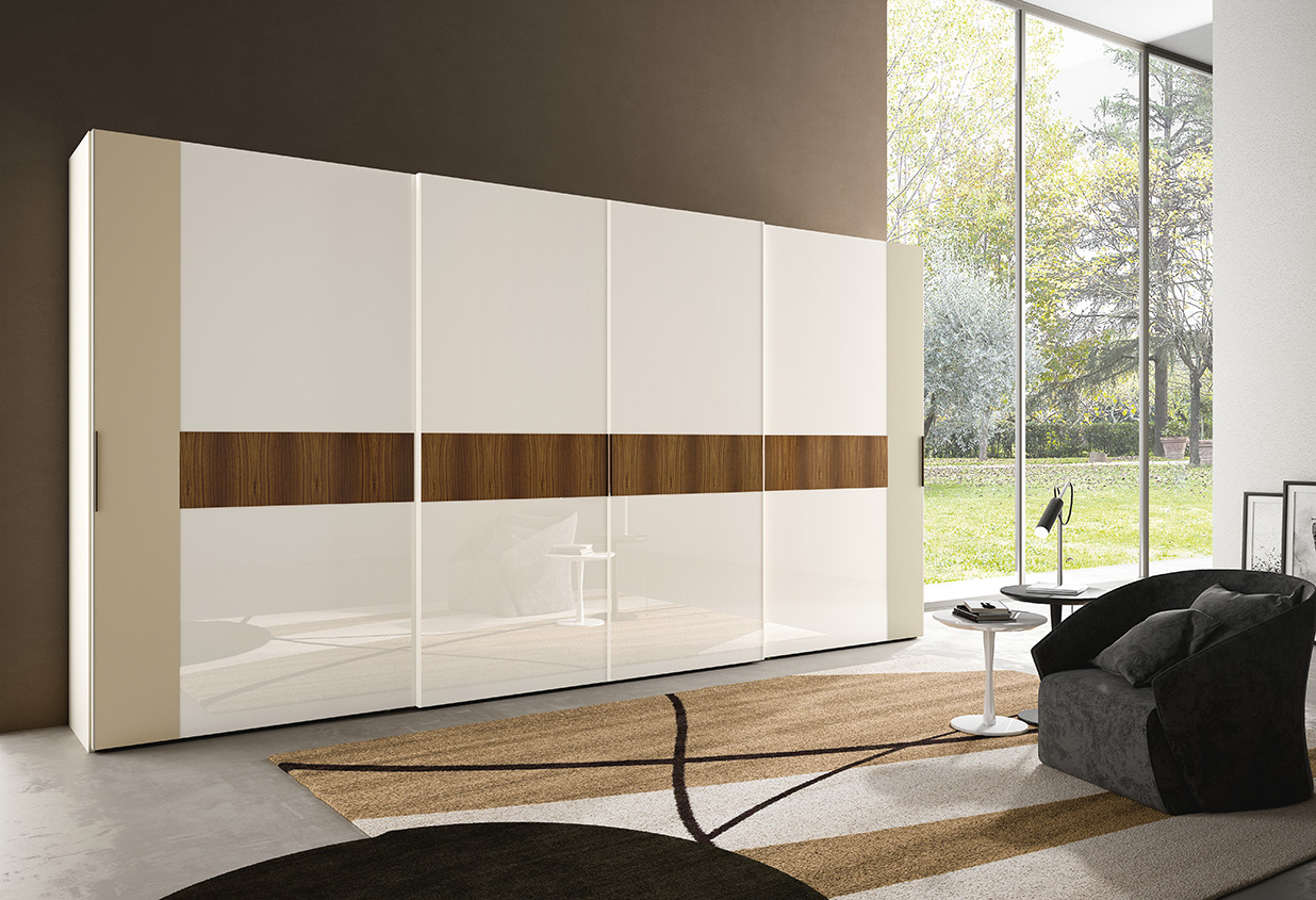 DESIGNER WALTER TURINI <br> Wardrobe with 4 sliding doors, solution with varying width doors: the doors at the extremes are wider because of the external section, champagne matt lacquered (L30). Central section with antique white lacquered glass (V062).