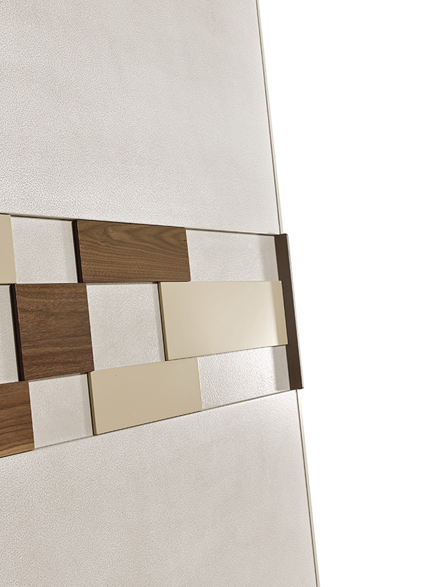DESIGNER WALTER TURINI <br> The SOHO applications on the wardrobe and central drawer of the dresser and nightstand, through a combination of different tile thicknesses and finishes, give a modern, sought-after look.
