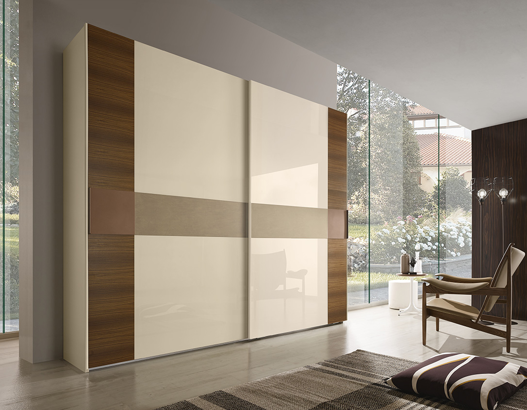 DESIGNER WALTER TURINI<br> Wardrobe with 2 sliding doors, external door section in Canaletto walnut with lacquered CORTEN-effect central tile. Central door section with champagne lacquered glass (V030) and cement-effect lacquered horizontal section.
