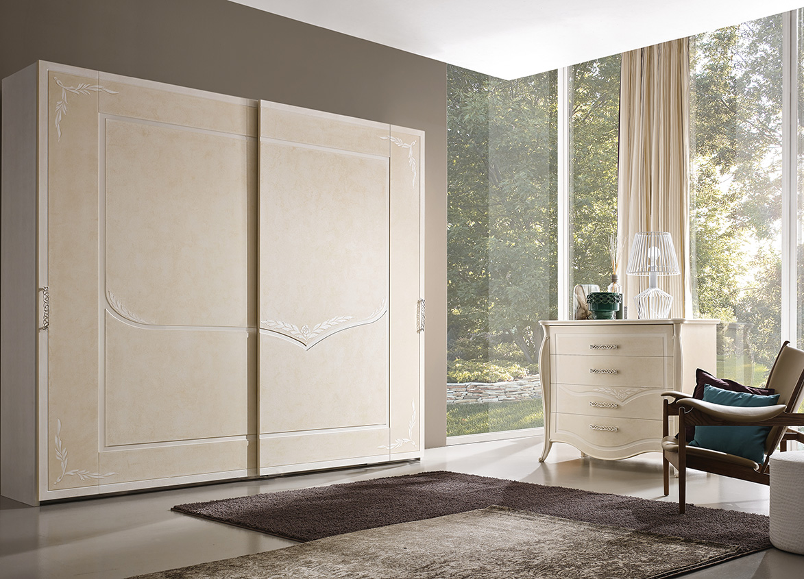 DESIGNER LEONARDO CIAMPI <br> Wardrobe with 2 sliding doors, ivory sponge finish with white glaze and decorations. Also available with external mirrors. Dresser with 4 curved drawers, ivory sponge finish with white glaze and decorations.