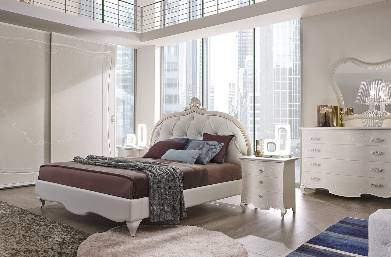 DESIGNER LEONARDO CIAMPI <br> Wardrobe with 2 sliding doors, grey sponge finish with white glaze and decorations. Dresser and nightstands, grey sponge finish with white glaze and decorations. Drawer fronts with waved contouring. Bed with capitonné upholstered headboard and cornice with frieze, upholstered bed surround with Chippendale feet.
