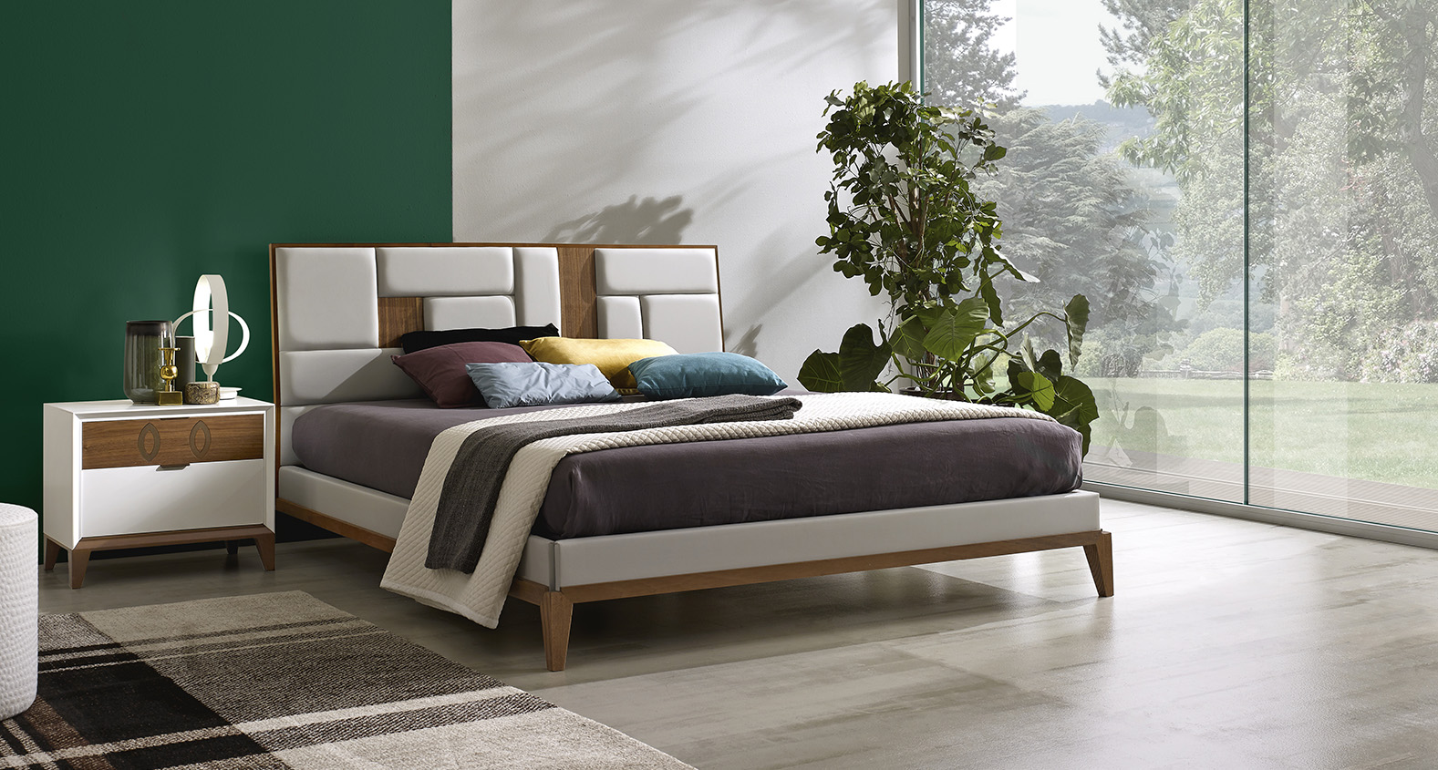 DESIGNER WALTER TURINI <br> Bed with tile-upholstered headboard and inserts in Canaletto walnut, bed surround with pedestal and feet in Canaletto walnut, side panels in faux leather.