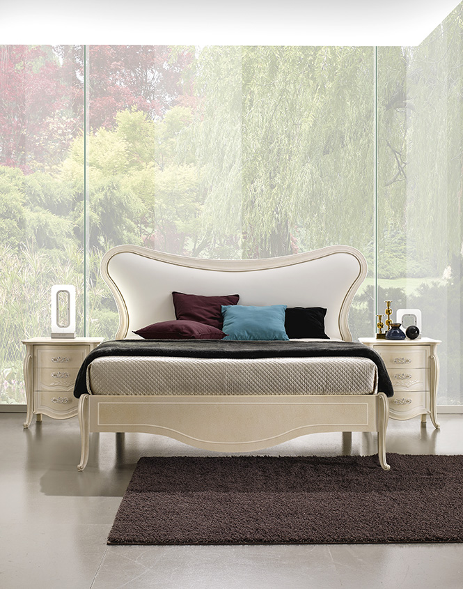 DESIGNER LEONARDO CIAMPI <br> Bed with upholstered headboard cornice and wooden bed surround.